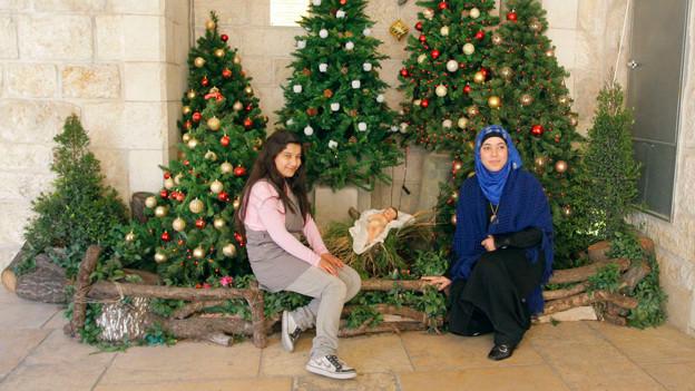 Friedliches Miteinander: Muslime posieren vor Weihnachtsbäumen in Bethlehem