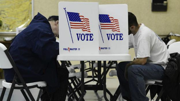 Zwei Männer füllen in Wichita im Bundesstaat Kansas ihren Wahlzettel aus