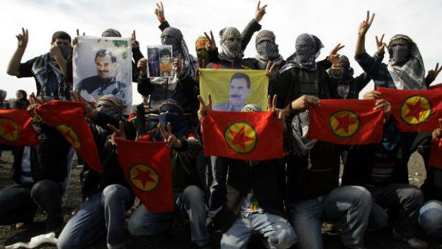 Maskierte Männer posieren mit dem Bild des Kurdenführers Abdullah Öcalan.