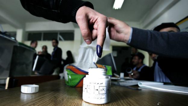 Ein Wähler in der jordanischen Hauptstadt Amman, der seinen Finger nach der Stimmabgabe in Tinte tunkt.