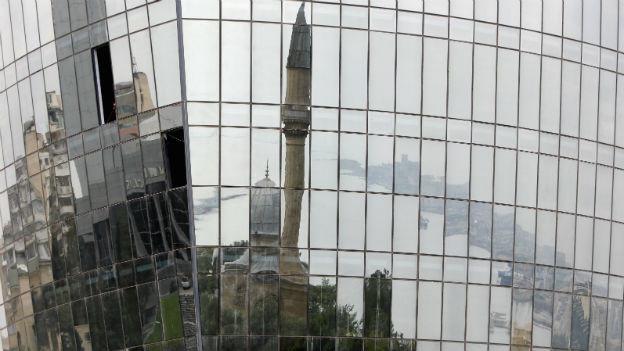 Moschee und Häuserfronten widerspiegeln sich in der Fassade eines Hochhauses in Baku.