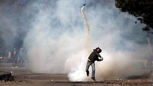 Ein Demonstrant wirft eine Tränengas-Granate bei Protesten in Kairo.