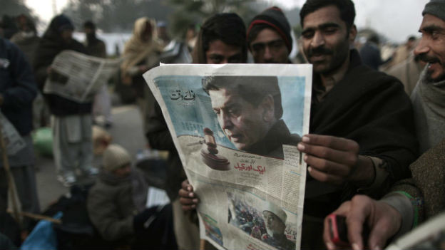 Qadri-Anhänger lesen die Schlagzeilen zur Verhaftung von Premier Ashraf