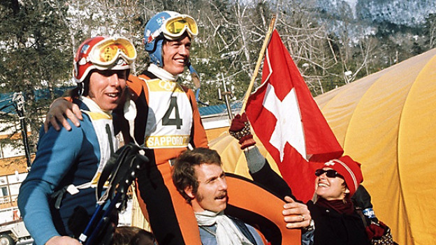 Der Schweizer Abfahrts-Olympiasieger Bernhard Russi (Nr. 4) und der Silbermedaillengewinner Roland Collombin auf den Schultern von Fans an den Olympischen Winterspielen in Sapporo 1972.