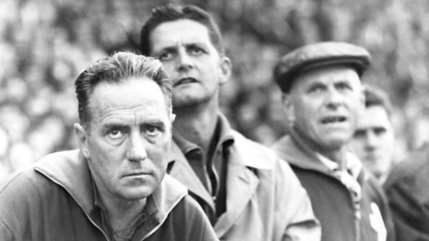 Alfredo Foni (links), Coach der Schweizer Fussballnationalmannschaft, beobachtet ein Spiel am 11. November 1964 mit ernster Miene.