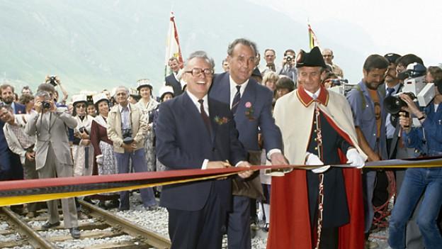 Bundesrat Leon Schlumpf, Vorsteher des Eidgenoessischen Verkehrs- und Energiewirtschaftsdepartementes EVED, durchtrennt am 25. Juni 1982 in Oberwald das Band und eröffnet feierlich den Furkatunnel.