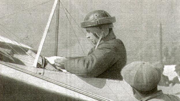 Etwas verschwommene Schwarz-Weiss Fotografie mit dem Piloten in seinem kleinen Eindecker.