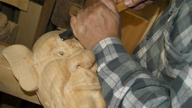 Markus Kläger schnitzt für die Waldkoboldä eine Holzmaske.