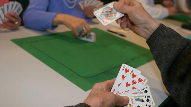 Ein Spieler spielt eine Jasskarte aus.