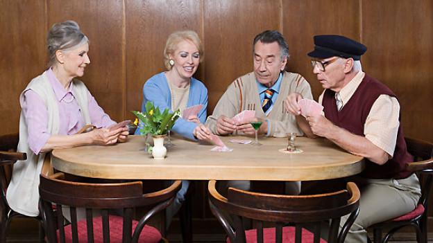 Vier Menschen Jassen an Tisch.