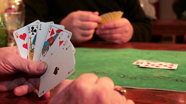 Zwei Spieler mit Jasskarten in der Hand.