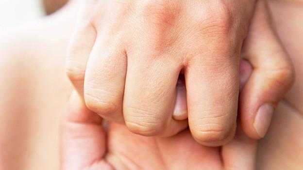 Zwei Hände, die ineinander greifen.