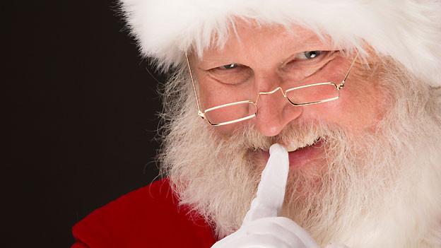 Ein bärtiger Weihnachtsmann mit Brille hält den Zeigefinger vor den Mund.