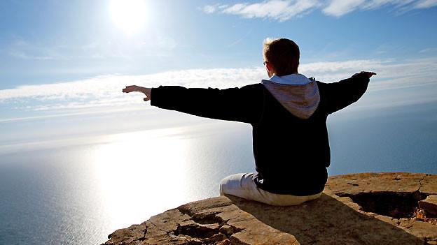 Ein Mann sitzt mit ausgebreiteten Armen auf einem Felsen, vor sich die unendliche Weite des Meeres.