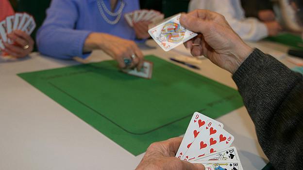 Ein Mann spielt eine Jasskarte aus.