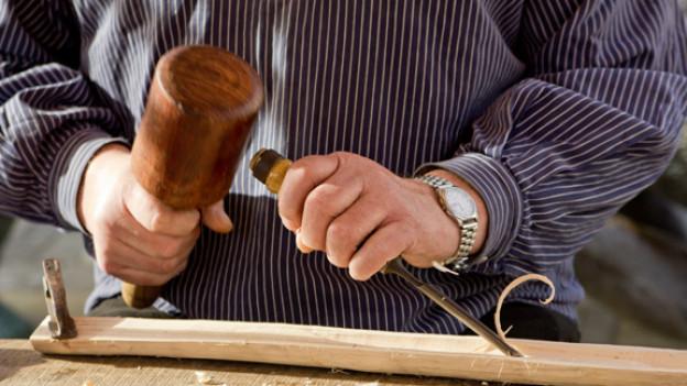 Ein Mann schnitzt Holz.