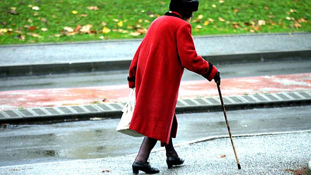 Diese Seniorin macht es genau richtig. Sie trägt einen auffällig, roten Mantel und geht auf dem Trottoir.