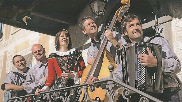 Ländleformatin auf Balkon mit Instrumenten und Tracht.