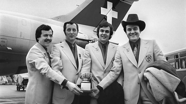 Erstmals in der Geschichte des Curlings wurde im schottischen Perth eine Schweizer Mannschaft Weltmeister. Das erfolgreiche Quartett vom Curling Club Crystal Zürich: Ueli Mülli, Rolf Gautschi, Roland Schneider und Skip Otto Danieli (v.l.n.r.) posiert am 28. März 1975 vor einem Flugzeug der Swissair auf dem Flughafen Zürich-Kloten mit der gewonnen Weltmeister-Trophäe.