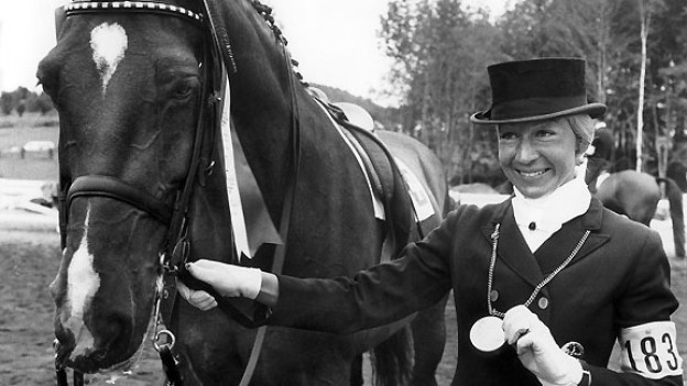 Die Dressurreiterin steht neben ihrem Pferd und zeigt lachend ihre Goldmedaille.