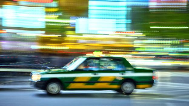 Damals wie heute: Ein Taxi auf rasanter Fahrt durch Tokio.