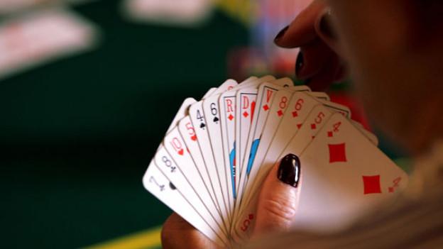 Frau mit schwarz gefärbtem Fingernagel hält Jasskarten in der Hand.