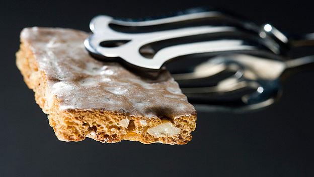 Das Basler Läckerli wird mit folgenden Zutaten zubereitet: Weissmehl, Honig, Zucker, Zimt, Muskat, Nelkenpulver, Mandeln oder Haselnüsse, Orangeat, Zitronat und Kirsch als Triebmittel.