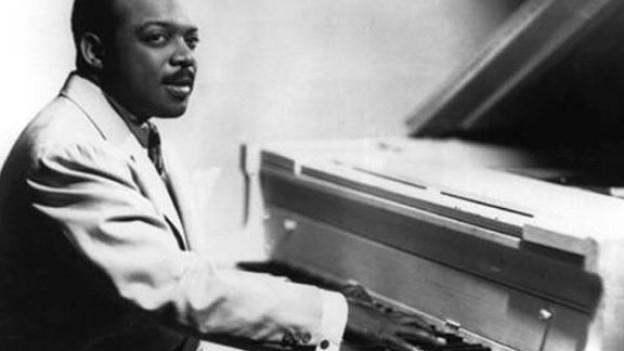 Der Musiker sitzt in einem hellen Anzug am Klavier.