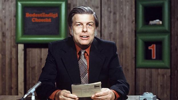 Ein Fernsehmoderator sitzt mit seinem Manuskript an einem Tisch vor einem Mikrofon.
