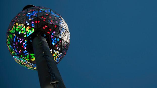 Eine grosse Kugel mit leuchtenden Dreiecken in verschiedenen Farben.