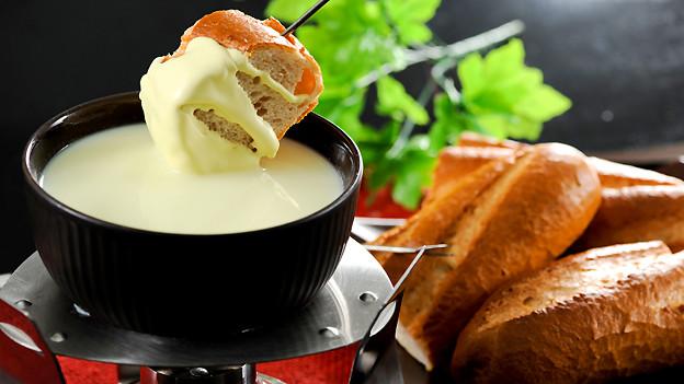 Eine kleine Schüssel mit Fondue, darüber ein kleines Stück Brot, an dem flüssiger Käse klebt.