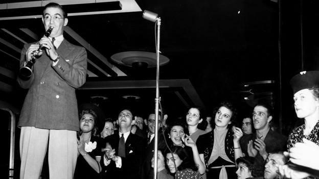 Banldeader Benny Goodman an der Klarinette - Die Aufnahme entstand 1938 bei einem Konzert mit seiner Band im Roseland Ballroom in New York City.