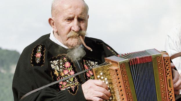 Musiker mit Schwyzerörgeli und Brissago im Mund.
