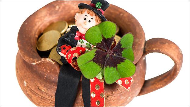 Versprechen jede Menge Glück: Ein Kaminfeger mit einem vierblättrigen Kleeblatt auf einem Topf voller Münzen.