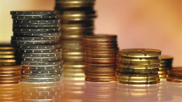 Mehrere Stapel mit glänzenden Münzen.