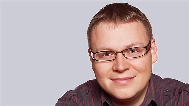 Porträt von einem Mann mit blonden Haaren und Brille.