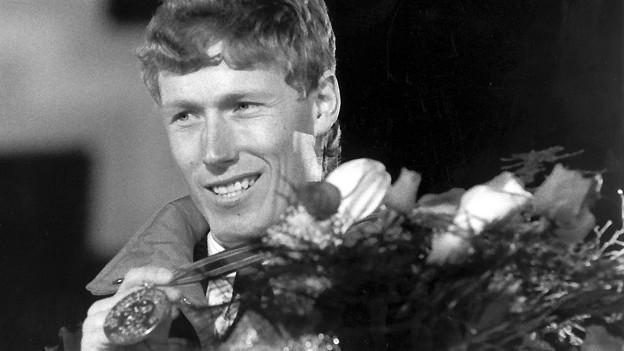 In einer Zeit von 1:59,63 Minuten gewinnt Pirmin Zurbriggen am 15. Februar 1988 bei den XV. Olympischen Winterspielen in Calgary die Abfahrt. Bei der Siegerehrung präsentiert der Walliser stolz seine Goldmedaille.