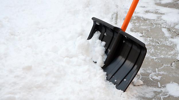 Schneeschaufel im Einsatz auf verschneitem Kopsteinpflaster.