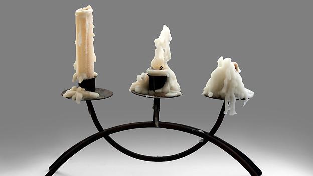 Ein schwarzer Kerzenständer mit drei unterschiedlich stark abgebrannten Kerzen, die allesamt viel Wachsspuren hinterlassen haben.