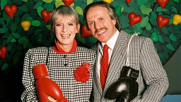 Schäppi und Müller in Kostüm vor Kulisse der TV-Sendung Traumpaar (Baum mit herförmigen Äpfen und Birnen).