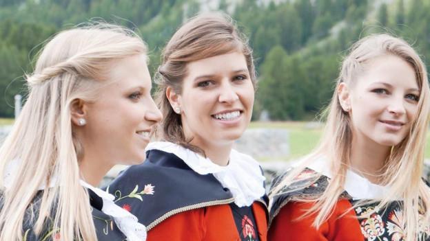 Drei junge Frauen in roter, Engadiner Sonntagstracht.