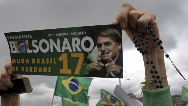 Wahlveranstaltung in Brasilien, eine Frau hält ein Plakat für Bolsonaro in die Luft