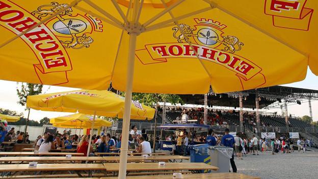 Sonnenschirm mit Alkoholwerbung an einem Turnfest.