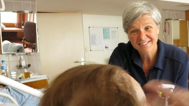 Eine Frau sitzt am Spitalbett einer älteren Frau und spricht mit ihr.