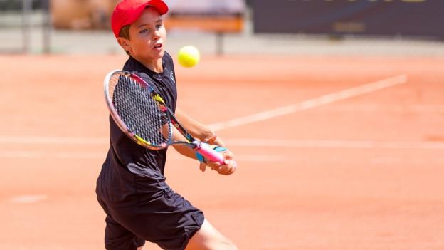 Knabe beim Tennisspielen.