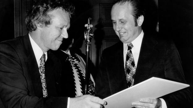 Der Schriftsteller Rolf Hochhuth, rechts, erhaelt am 3. Dezember 1976 in Basel von Regierungsrat Lukas Burckhardt, links, den Kunstpreis der Stadt Basel ueberreicht.