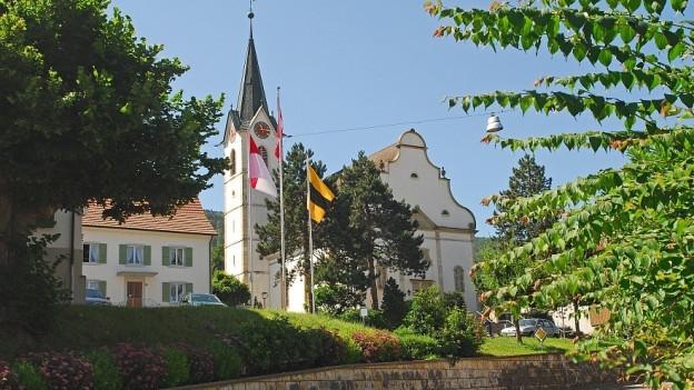 Dorfkirche vom Metzerlen mit Fahnen davor