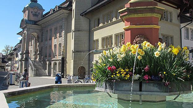 Dorfbrunnen mit BLumen vor Rathaus.