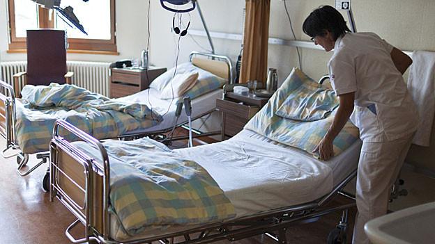 Eine Pflegerin richtet ein Bett.