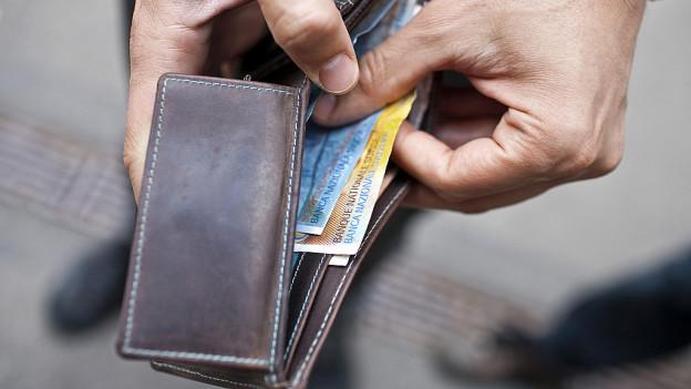 Eine Hand greift in ein Portemonnaie.